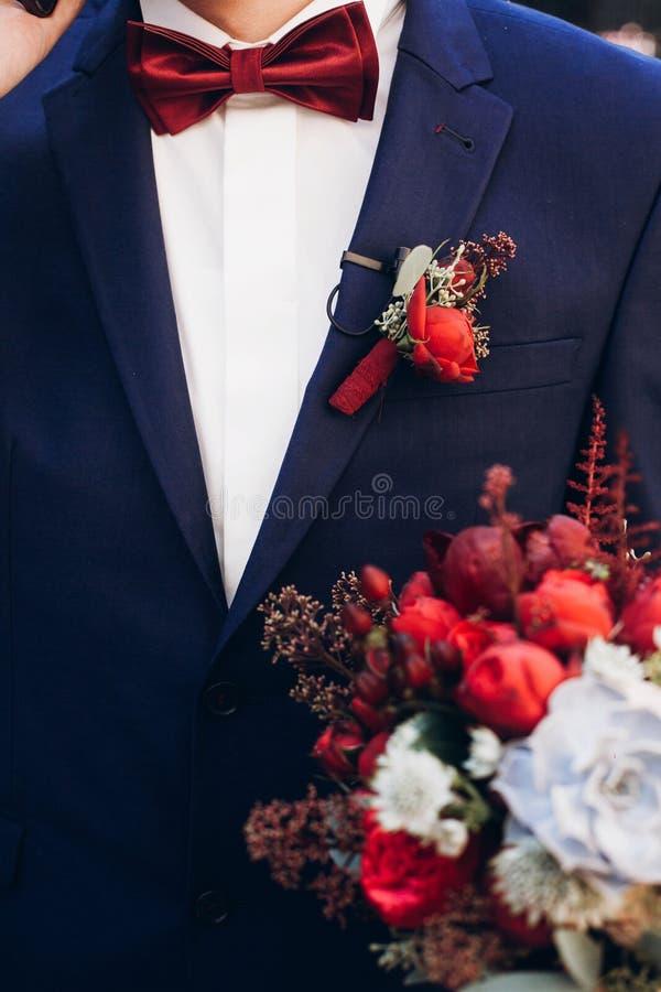 Het boeket van de bruidegomholding met rode rozen en succulents in morni royalty-vrije stock foto