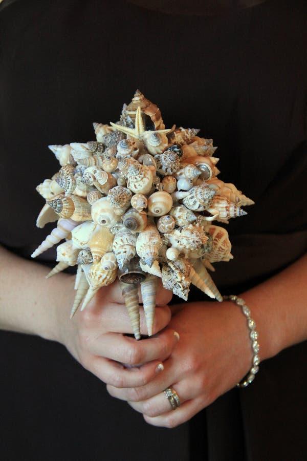 Het boeket van de bruidsmeisjeholding van zeeschelpen stock afbeelding