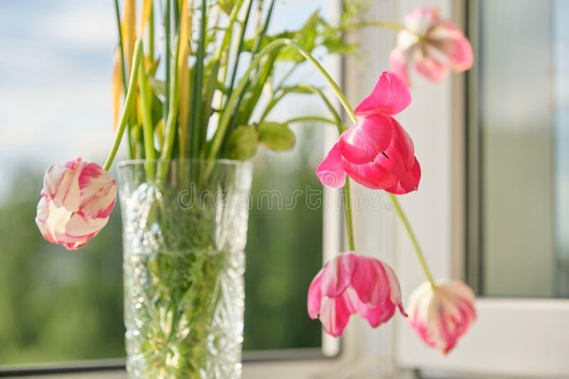 Het boeket van de lente bloeit tulpen en witte gele narcissen in vaas op het venster stock foto