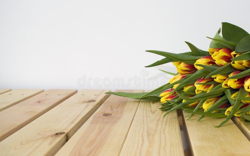 Het boeket van de lentepasen van tulpenbloemen op houten achtergrond stock afbeelding