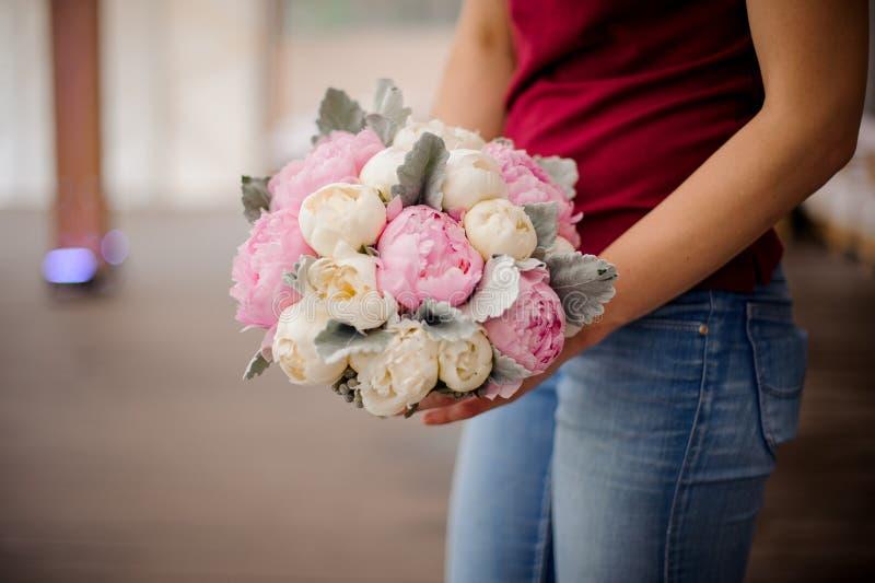 Het boeket van de meisjesholding van roze en van de champagnekleur pioenen stock fotografie