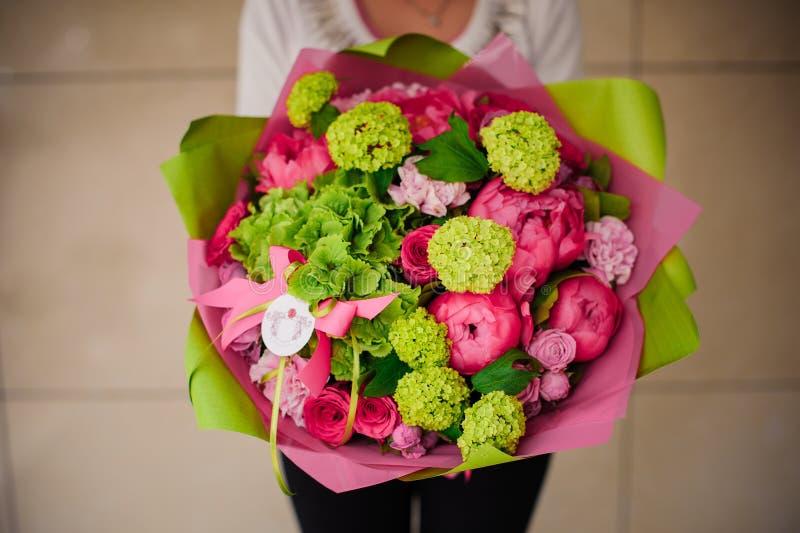 Het boeket van de meisjesholding van roze en groene bloemen stock foto's