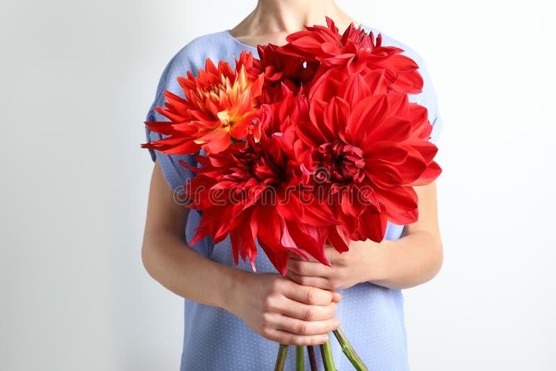 Het boeket van de vrouwenholding van mooie dahliabloemen stock foto