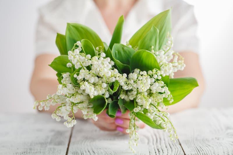 Het boeket van de vrouwenholding van lelietje-van-dalenbloemen stock afbeelding