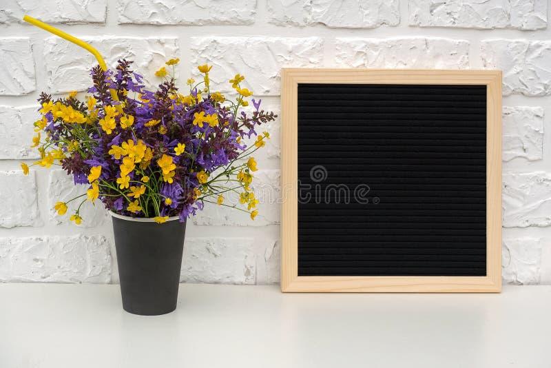 Het boeket van gekleurde bloemen in zwarte document koffiekop met cocktailstro en de lege zwarte brief schepen op lijst in tegen  royalty-vrije stock afbeelding