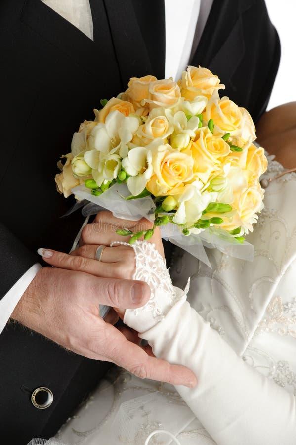 Het boeket van het huwelijk in handen van bruid en bruidegom, op wh stock fotografie