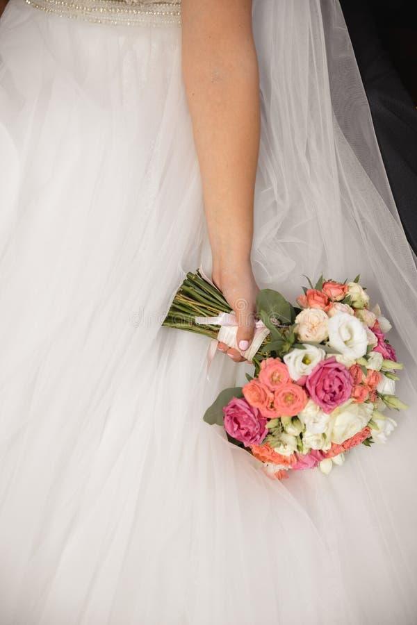 Het boeket van huwelijksbloemen in de hand van de bruid - Bruid in huwelijkskleding royalty-vrije stock foto
