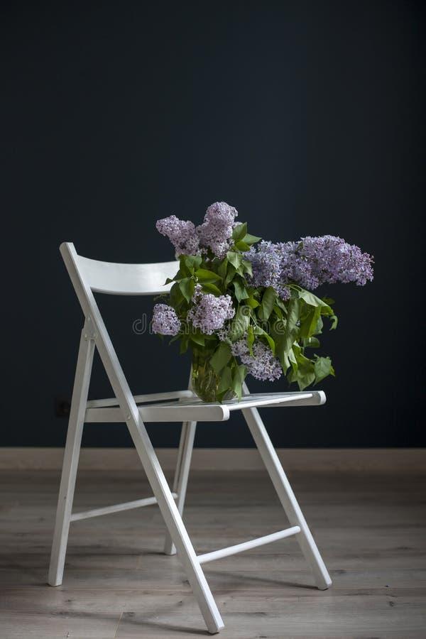 Het boeket van lilac takjes in een transparante groene kruik op de witte stoel als decoratie van binnenland tegenovergesteld van  royalty-vrije stock afbeelding