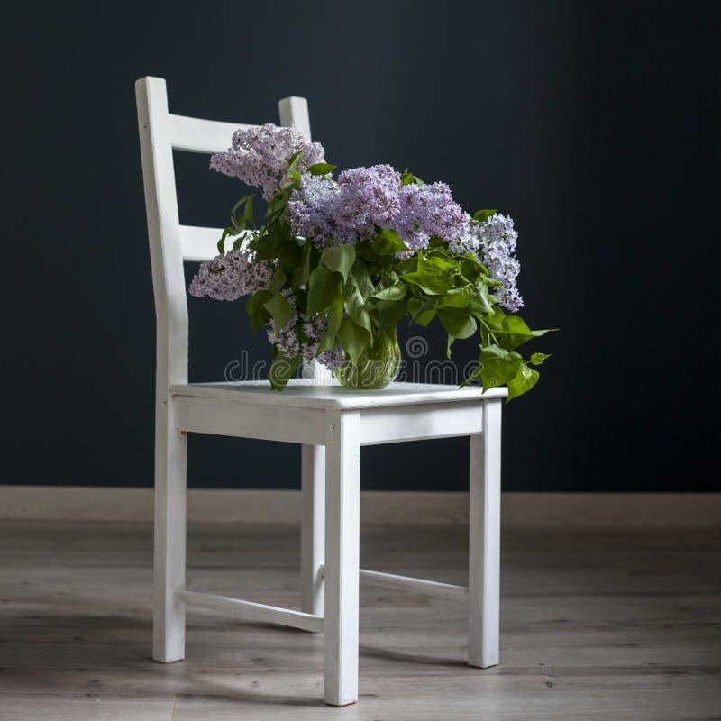 Het boeket van lilac takjes in een transparante groene kruik op de witte stoel als decoratie van binnenland tegenovergesteld van  stock afbeeldingen