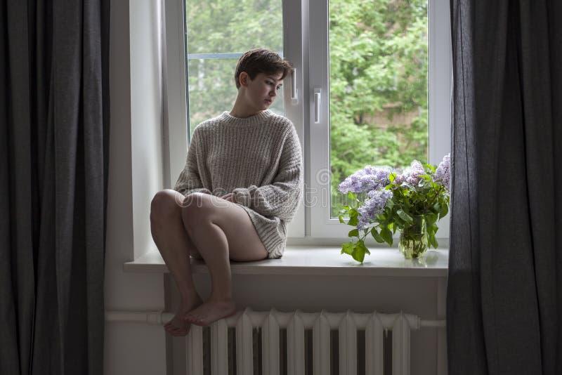 Het boeket van lilac takjes in een transparante kruik op witte stoel als decoratie van binnenland Het meisje zit op het venster stock afbeelding