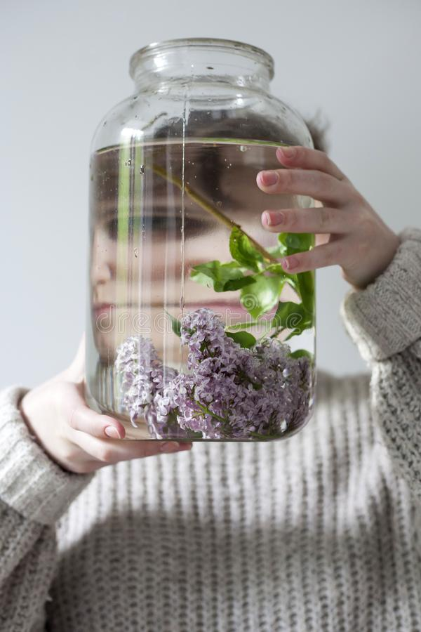 Het boeket van lilac takjes in een transparante kruik op witte stoel als decoratie van binnenland Het meisje zit op het venster royalty-vrije stock afbeeldingen