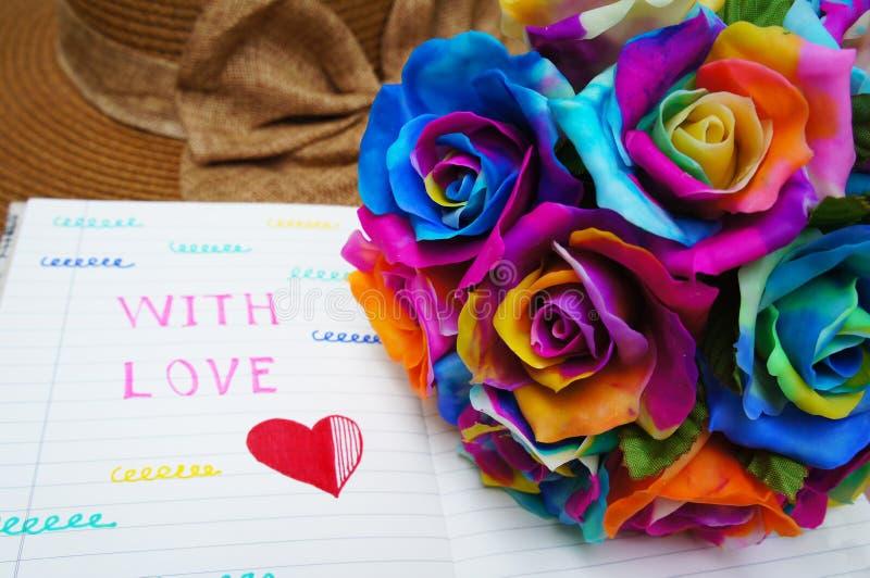 Het boeket van regenboogrozen, multi-colored rozen met notaboek stock afbeeldingen