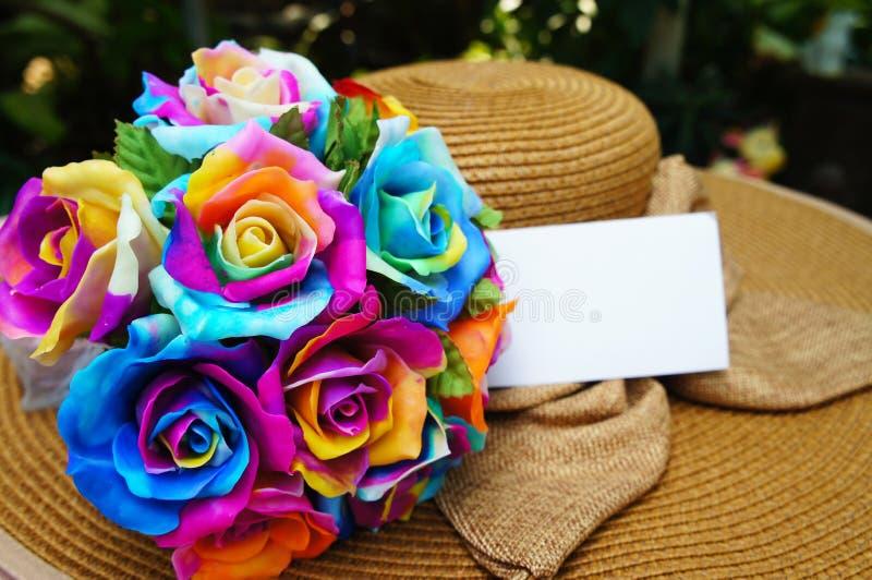 Het boeket van regenboogrozen, multi-colored rozen met witte giftkaart stock foto's