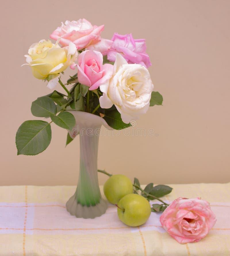 Het boeket van rozen in pastelkleuren in een vaas met appelen op lijst, stilleven stock foto