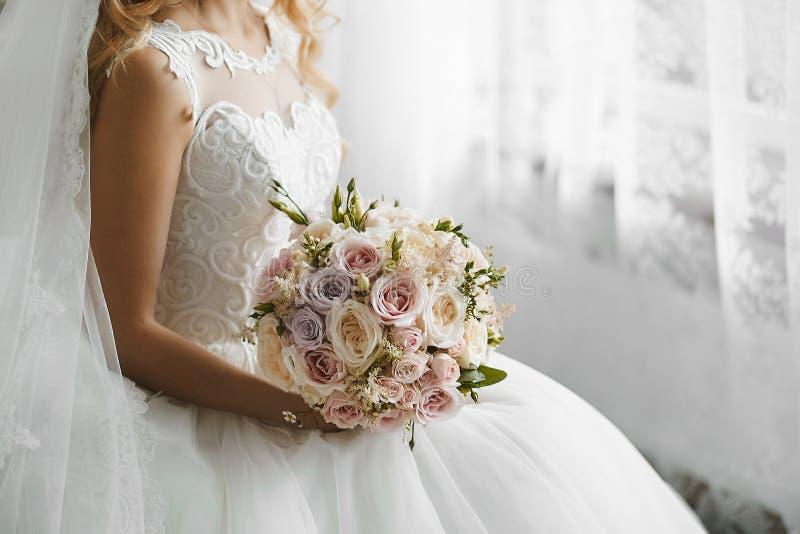 Het boeket van vers nam en pioenenbloemen binnen in de handen van een mooie jonge blondevrouw in modieuze huwelijkskleding toe stock fotografie