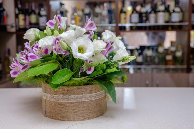 Het boeket van verse bloemen in textielpot op de barteller royalty-vrije stock foto