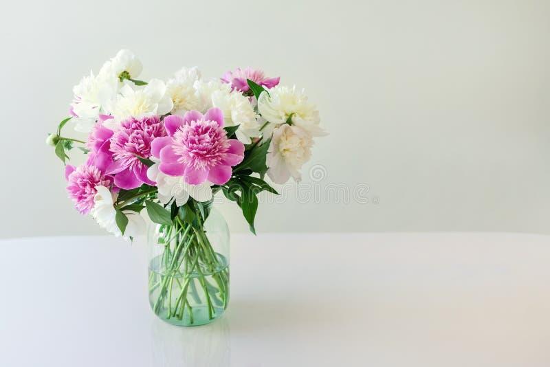 Het boeket van verse grote roze, witte en roompioenen in eenvoudige glaskruik op blik dient binnen in Vaas met de mooie tedere le stock foto