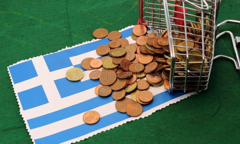 Het boodschappenwagentjehoogtepunt van euro muntstukken viel Vlag van Griekenland om stock foto