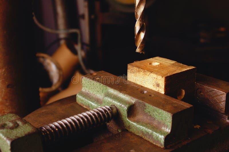 Het boorbeetje die neer op een stuk van hout komen hield in een ondeugd in een industriële workshop stock foto