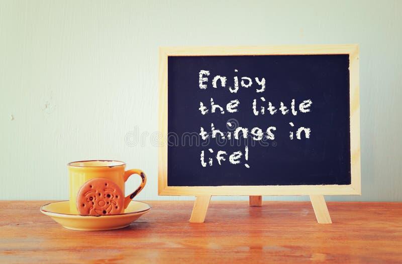 Het bord met de uitdrukking geniet van de kleine dingen in het leven naast koffiekop over houten lijst royalty-vrije stock foto's