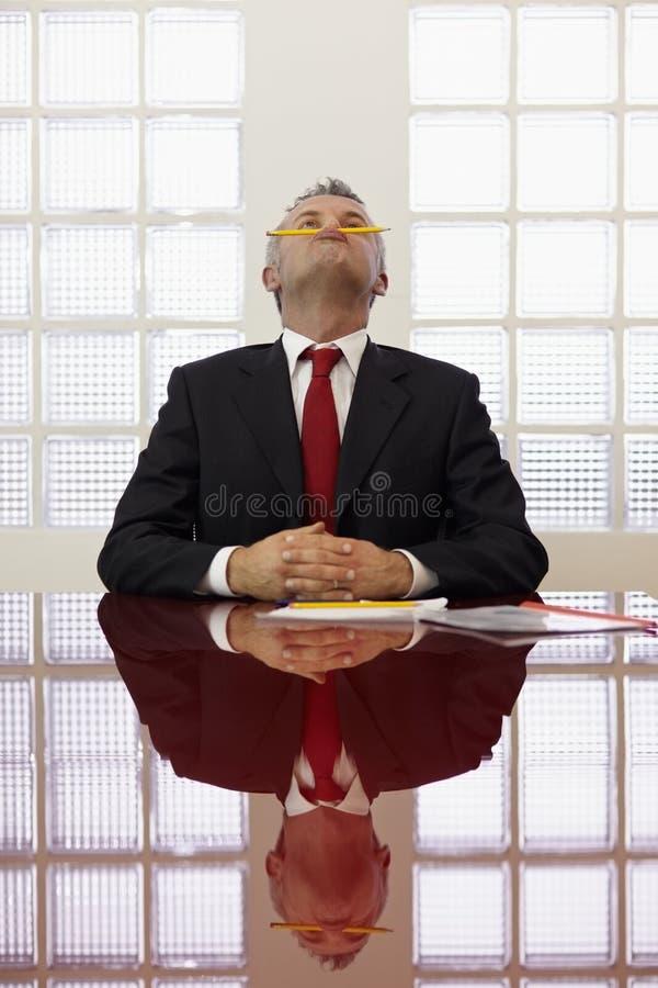 Het Bored mens spelen met potlood op het werk royalty-vrije stock foto's
