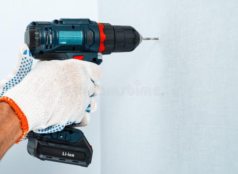 Het boren van de muur met een draadloze boor in beschermende handschoenen royalty-vrije stock foto