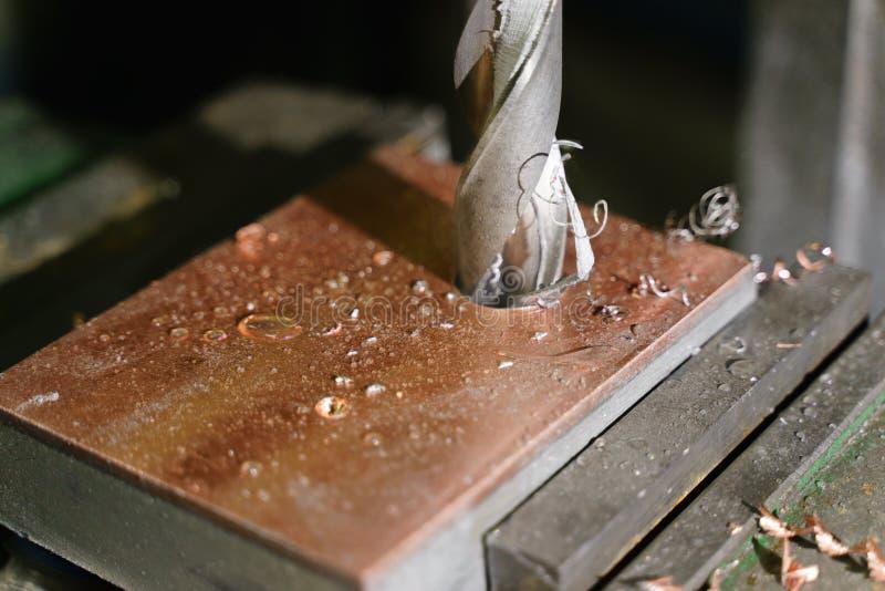 Het boren van een gat met een boringsmachine in een katrol van het metaalwerkstuk, close-up, de industrie royalty-vrije stock fotografie
