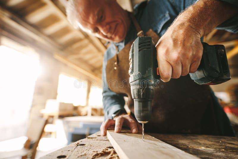 Het boren van een gat op houten plank stock afbeelding