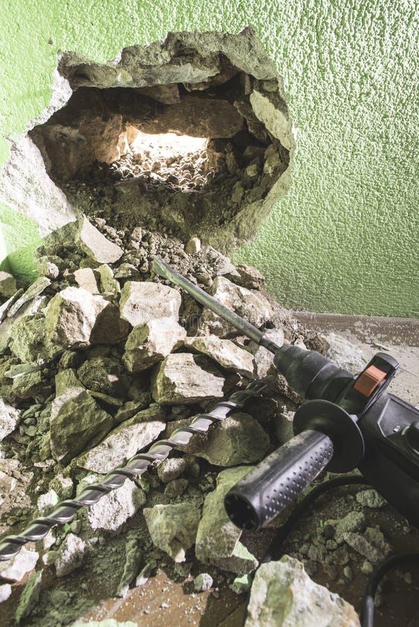 Het boren van een groot gat in de muur stock afbeelding