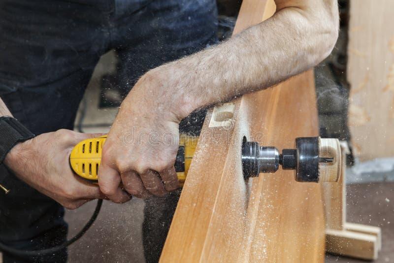 Het boren van het gat voor deurhandvat die elektrische boor, close-up gebruiken stock afbeelding