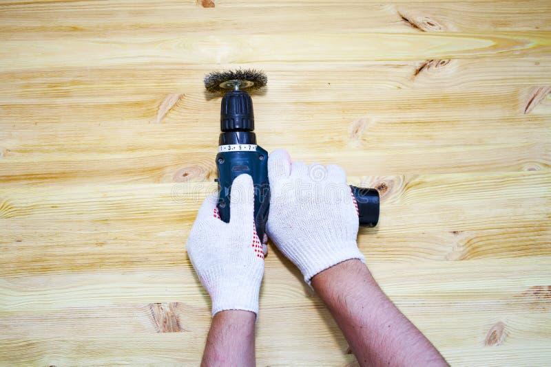 Het het borstelen proces van houten plank De mannelijke hand houdt het borstelen machine het elektro roteren met de schijf die va stock afbeelding