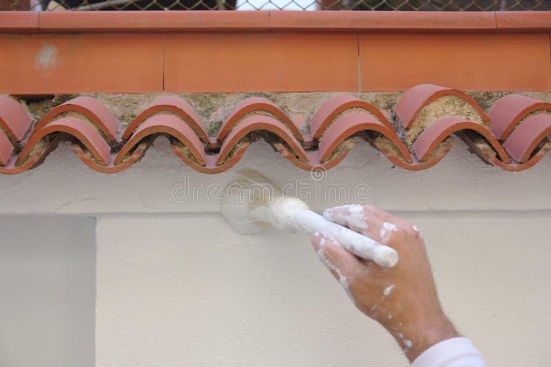 Het borstelen van de details op een witte muur stock afbeeldingen