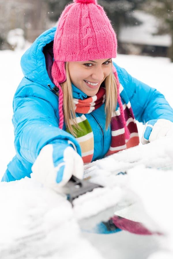 Het borstelen van de vrouw sneeuw van de winter van de autovoorruit stock afbeeldingen
