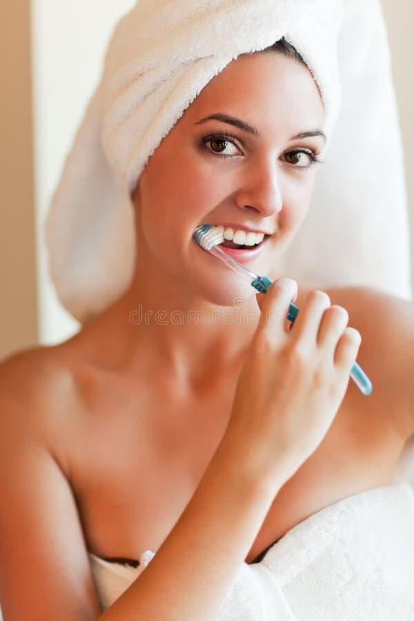Het borstelen van de vrouw tanden stock fotografie