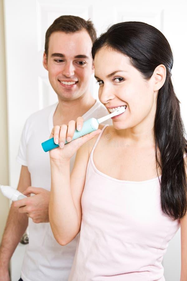 Het borstelen van het paar tanden in de badkamers stock afbeelding