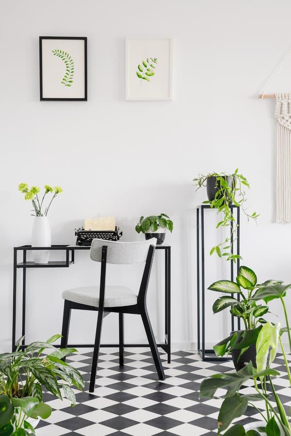Het botanische binnenland van het huisbureau met een bureau, een stoel en een grafiek op de muur Echte foto stock afbeeldingen