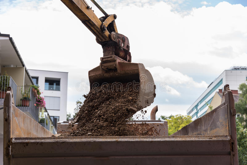Het bouwafval wordt geladen door graafwerktuigschop stock foto's
