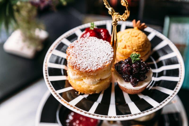 Het bovenste laagje van de sconepastei met suikerglazuur en Bosbes Mini Tart op zwart-witte plaat dessert voor middagthee royalty-vrije stock foto