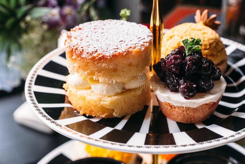 Het bovenste laagje van de sconepastei met suikerglazuur en Bosbes Mini Tart op zwart-witte plaat dessert voor middagthee royalty-vrije stock foto's