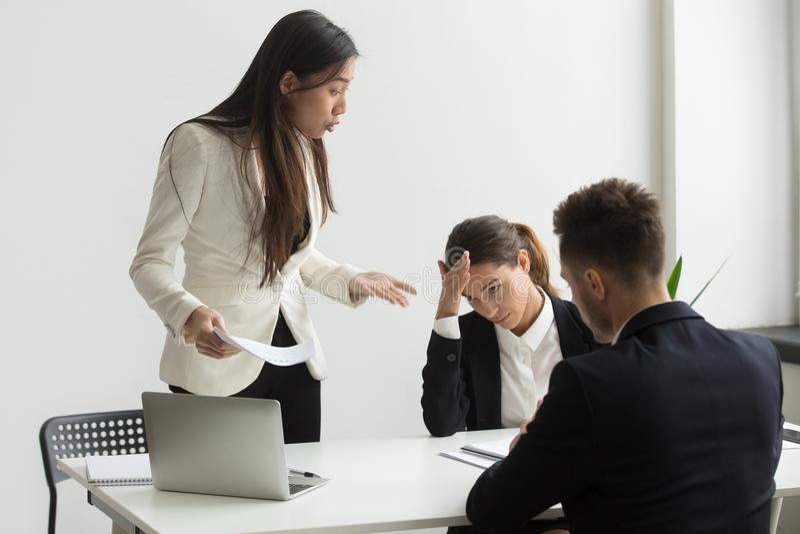Het boze Aziatische uitvoerende schreeuwen bij ondergeschikten die voor slecht berispen stock foto
