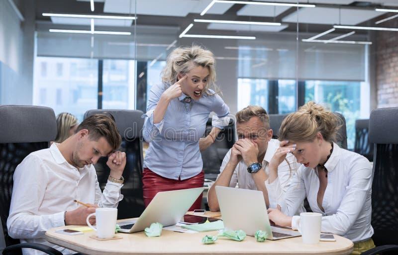 Het boze chef- schreeuwen bij werknemers stock foto's