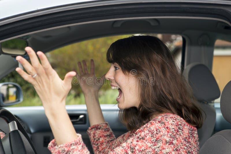 Het boze jonge vrouw drijven in auto stock foto's