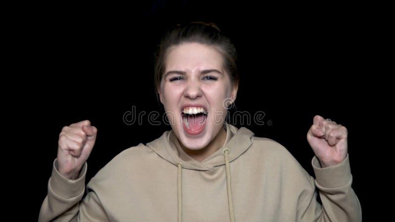 Het boze jonge vrouw gillen geïsoleerd op zwarte achtergrond Woedend gemaakt wijfje die op zwarte achtergrond, waanzinconcept gil stock foto