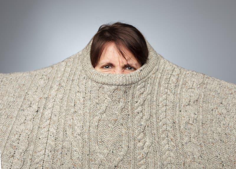 Het boze meisje trekt een grote gebreide sweater over haar hoofd royalty-vrije stock afbeelding