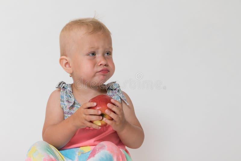 Het boze peutermeisje zit en houdt rode appel stock fotografie