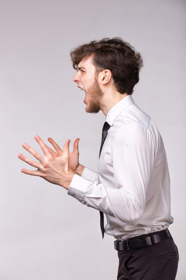 Het boze woedende zakenman schreeuwen uit luid met handen omhoog over grijze achtergrond stock foto