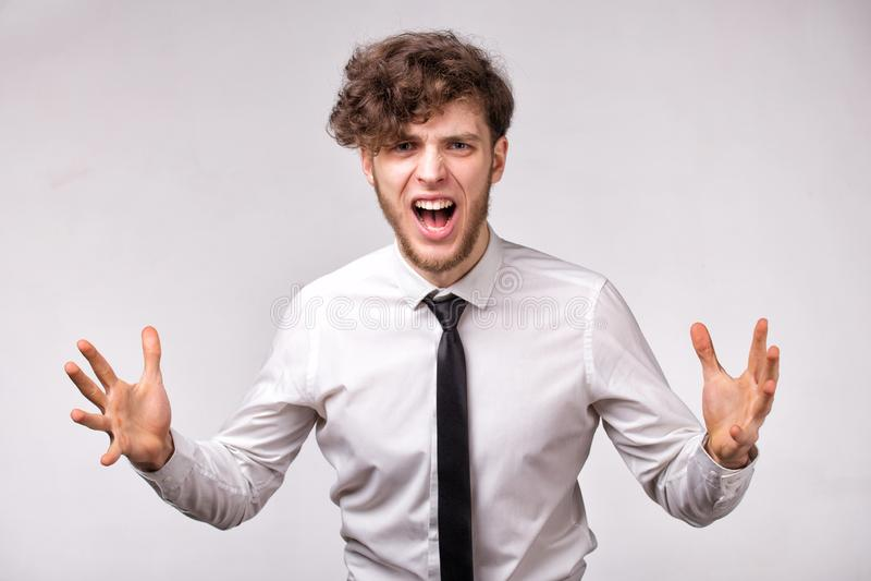 Het boze woedende zakenman schreeuwen uit luid met handen omhoog over grijze achtergrond stock fotografie