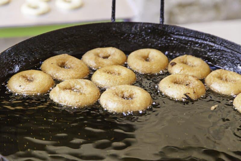 Het braden donuts in een markt stock foto's