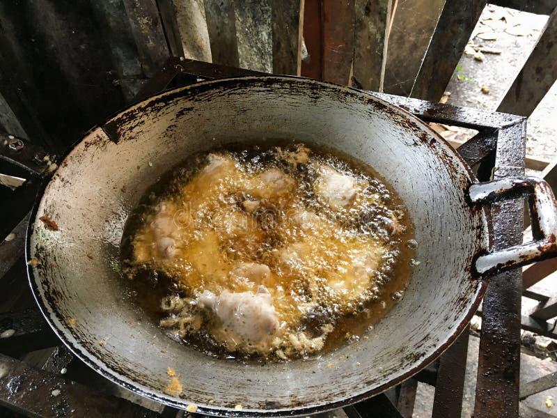 Het braden van kip in hete olie stock foto