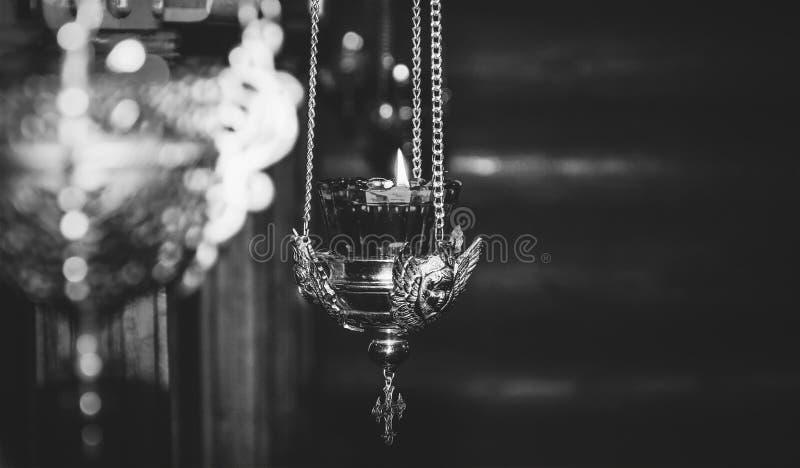 Het branden licht in een oude lamp van de koperkerk met het beeld van een engel stock foto's